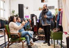 Amici che scelgono i vestiti al negozio di vestiti d'annata Fotografie Stock Libere da Diritti