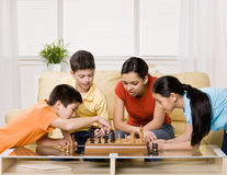 Amici che si raccolgono per giocare scacchi Immagini Stock