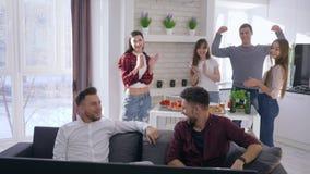 Amici che si rilassano sullo strato che gioca i video giochi sulle consoli su backgrounf della società divertendosi dell'interno  stock footage