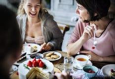 Amici che si riuniscono insieme sul godimento h dei dolci di cibo del ricevimento pomeridiano immagine stock