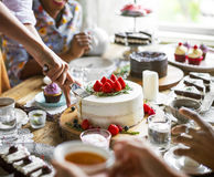 Amici che si riuniscono insieme sul godimento h dei dolci di cibo del ricevimento pomeridiano fotografia stock libera da diritti