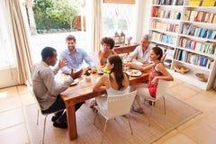 Amici che si siedono ad una tavola che parla durante il partito di cena fotografia stock libera da diritti
