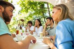 Amici che si siedono alla tavola in ristorante all'aperto Fotografie Stock Libere da Diritti