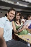 Amici che si siedono insieme nell'aula Immagine Stock