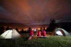 Amici che si siedono insieme sul banco e sul fuoco di sorveglianza accanto al campeggio Immagini Stock Libere da Diritti