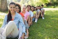 Amici che si siedono nella linea sulla città universitaria Fotografia Stock Libera da Diritti