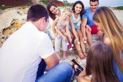 Amici che si siedono sulla sabbia alla spiaggia nel cerchio con marshmal Fotografie Stock Libere da Diritti
