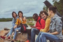 Amici che si siedono sulla spiaggia e che ascoltano la musica fotografia stock