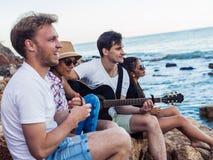 Amici che si siedono sulle pietre sulla spiaggia L'uomo sta giocando la chitarra Fotografia Stock