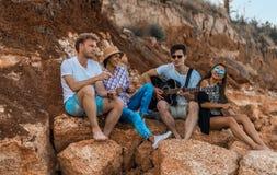 Amici che si siedono sulle pietre sulla spiaggia L'uomo sta giocando la chitarra Immagine Stock Libera da Diritti