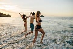 Amici che si tengono per mano e che corrono alla spiaggia Fotografia Stock