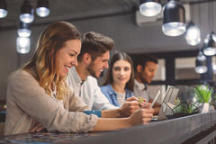 Amici che studiano insieme alla caffetteria immagini stock libere da diritti