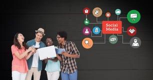 Amici che utilizzano gli apparecchi elettronici contro le icone sociali di media nel fondo Fotografia Stock Libera da Diritti