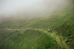 Amici che viaggiano insieme in montagna nebbiosa Fotografia Stock Libera da Diritti