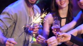 Amici con champagne e stelle filante su un partito stock footage