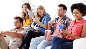 Amici con gli aggeggi e la birra che guardano TV a casa stock footage