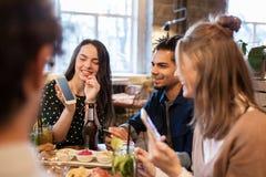 Amici con gli smartphones e l'alimento alla barra o al caffè Fotografia Stock Libera da Diritti