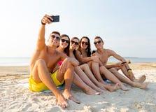 Amici con gli smartphones sulla spiaggia Fotografia Stock