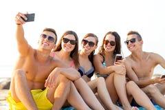 Amici con gli smartphones sulla spiaggia Immagine Stock