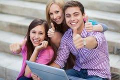 Amici con il computer portatile che mostra i pollici in su Fotografie Stock