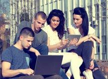 Amici con il computer portatile sul banco Immagini Stock