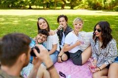Amici con le bevande che fotografano al picnic di estate fotografia stock libera da diritti