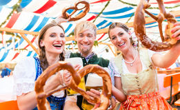 Amici con le ciambelline salate giganti in tenda bavarese della birra fotografia stock