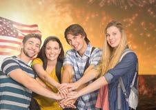 Amici con le mani insieme contro la bandiera americana ed i fuochi d'artificio Immagini Stock