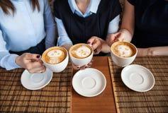Amici con le tazze di caffè in loro mani in un caffè Immagini Stock Libere da Diritti