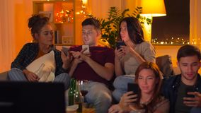 Amici con lo smartphone che guardano TV a casa archivi video