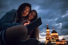 Amici con una compressa in una città di notte fotografia stock libera da diritti