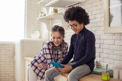 Amici contentissimi positivi che comunicano online con i compagni di classe fotografie stock