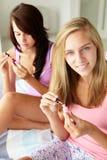 Amici degli adolescenti che verniciano i chiodi Fotografia Stock