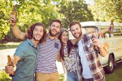 Amici dei pantaloni a vita bassa che mangiano una birra insieme Fotografia Stock