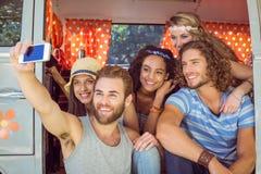 Amici dei pantaloni a vita bassa sul viaggio stradale che prende selfie Immagine Stock
