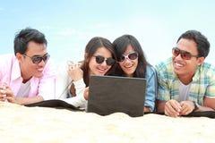 Amici del gruppo che godono della festa della spiaggia insieme al computer portatile Immagine Stock Libera da Diritti