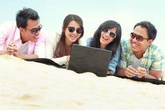 Amici del gruppo che godono della festa della spiaggia insieme al computer portatile Fotografia Stock Libera da Diritti