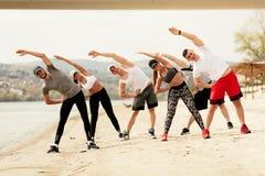 Amici del gruppo che si esercitano sulla spiaggia Fotografia Stock Libera da Diritti