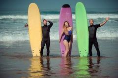 Amici del surfista su una spiaggia con bordi praticanti il surfing Fotografia Stock