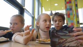 Amici dell'adolescente che guardano film nell'attimo mobile che mangia alimenti a rapida preparazione in pizzeria stock footage