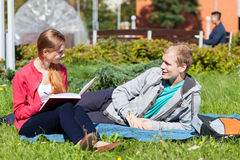 Amici dell'università che si siedono sull'erba Fotografia Stock Libera da Diritti