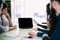 Amici dell'università che socializzano insieme e che studiano per l'esame in biblioteca Gruppo di studenti che si siedono alla ta Fotografia Stock