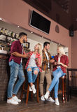 Amici della gente che bevono il contatore di Juice Talking Laughing At Bar, l'uomo arancio della corsa della miscela e le coppie  Fotografia Stock