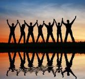 Amici della siluetta. acqua di tramonto Fotografie Stock