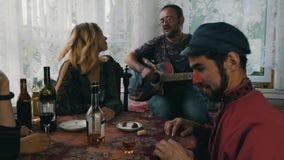 Amici della società sul terrazzo in casa di campagna Chitarra del gioco dell'uomo Uomo con il naso rosso stock footage