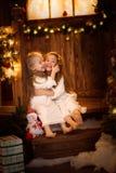 Amici della sorella delle ragazze che abbracciano seduta all'albero di Natale, concetto Immagini Stock