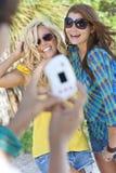 Amici delle giovani donne che catturano le maschere sulla vacanza Fotografia Stock Libera da Diritti