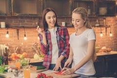 Amici delle giovani donne che cucinano insieme pasto a casa Fotografia Stock