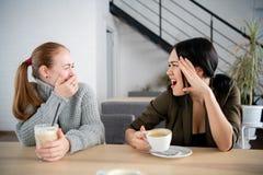 Amici delle giovani donne offensivi in caffè mentre bevendo caffè immagine stock libera da diritti