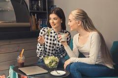 Amici delle giovani donne in un tempo libero della caffetteria Immagini Stock Libere da Diritti